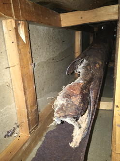 Broken cast iron drain pipe in a basement